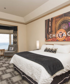 Hotel Room with Bed, painting with Chicago printed on it, and window with lake view.