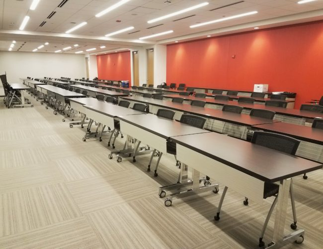Long rows of desks with chairs facing front in conference room
