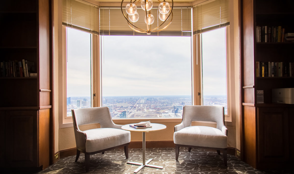 Hotel Lounge with Two Chairs, Small Table, and Large Window with View of City