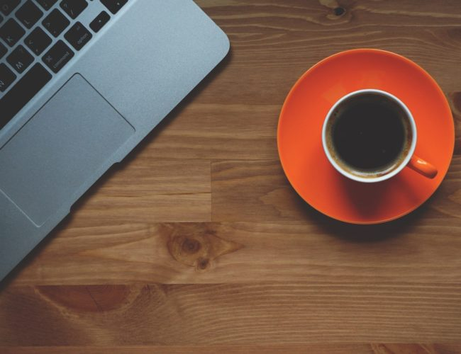 Cup of coffee on table next to computer